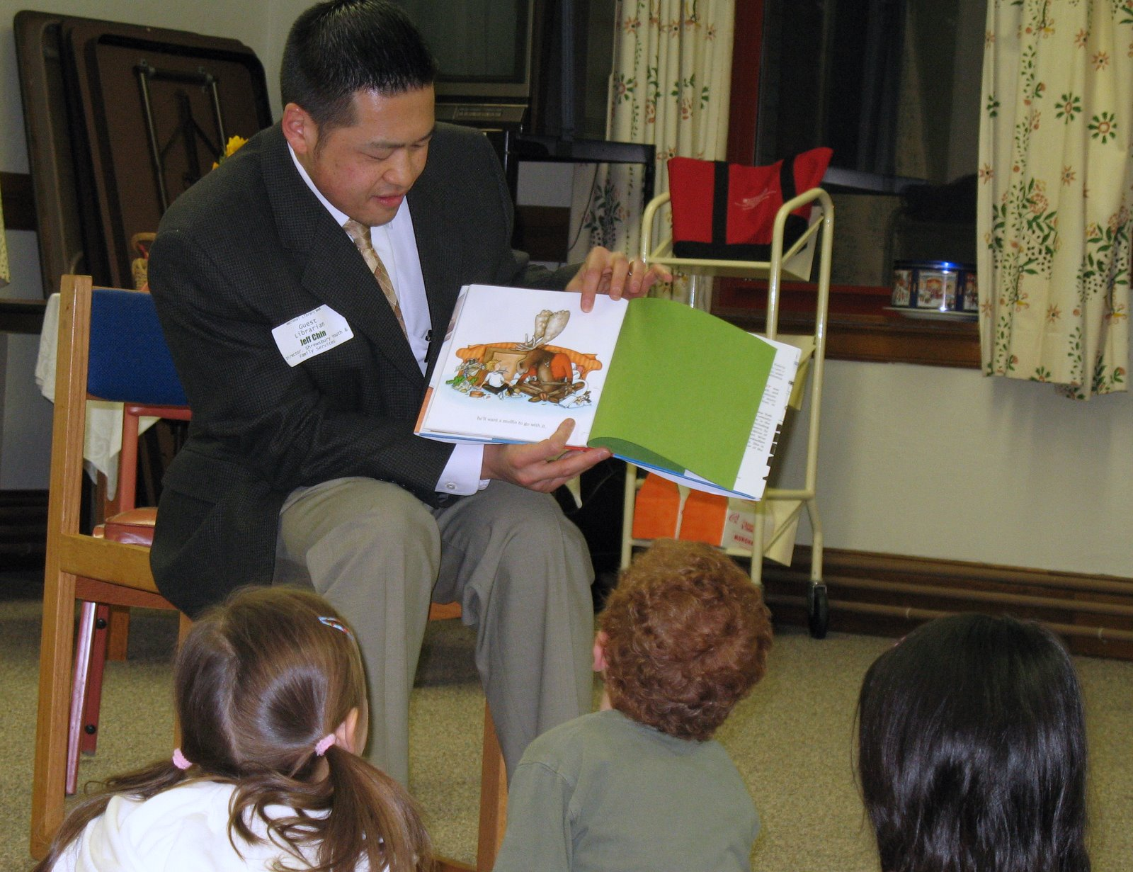 Man sitting on a chair and reading from a book to kids